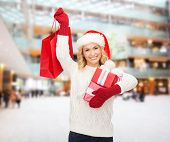 happiness, winter holidays, christmas and people concept - smiling young woman in santa helper hat with gifts and shopping bag over mall background
