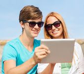 friendship, leisure, summer, technology and people concept - group of smiling friends with tablet pc