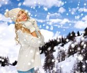 happiness, winter holidays, tourism, travel and people concept - smiling young woman in white hat and mittens over snowy mountains background