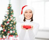 x-mas, winter, happiness, holidays and people concept - smiling woman in santa helper hat with small red gift box over living room and christmas tree background