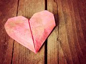 a discarded dirty paper origami heart on a wooden background toned with a vintage instagram filter effect applied (very shallow DOF on center crease)