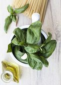 Ingredients for Pesto alla Genovese on wooden background - basil, parmesan, garlic, olive oil