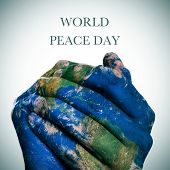 the sentence world peace day  and a world map in man hands forming a globe (Earth map furnished by N