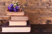 Books and wildflowers on wooden table on wooden wall background