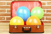 Pile of balloons of different colors in old suitcase, on brick wall background