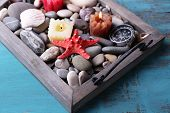 Candles on vintage tray with sea pebbles,starfish and sea shells on wooden background