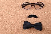 Glasses, mustache and bow tie forming man face on color background