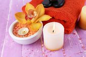 Still life with beautiful blooming orchid flower, towel and sea salt in bowl on color wooden backgro