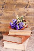Books and wildflowers on napkin on wooden table on wooden wall background