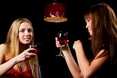 stock photo of ladies night  - Two young women drinking red wine in a bar - JPG