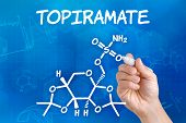 Hand with pen drawing the chemical formula of Topiramate