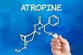 Hand with pen drawing the chemical formula of Atropine