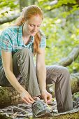 Hiker Tying Shoelaces In A Forest