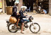 Black Hmong woman and man on motobike