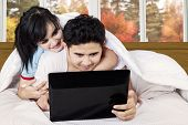 Asian Couple Using Laptop On Bed