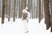 Young Mother Carrying Her Baby In The Forest On A Very Snowy Day