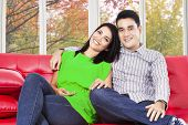 Couple Sitting On Sofa And Smiling At Camera