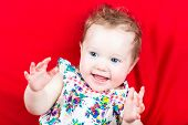Cute Laughing Baby Girl In A Summer Dress On A Red Blanket