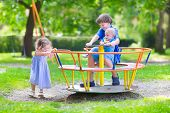 stock photo of three sisters  - Three happy children laughing teenager boy cute baby and adorable toddler girl brothers and sister playing together on a playground swing enjoying a sunny hot summer day - JPG