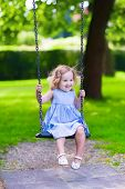 image of playground  - Happy laughing toddler girl with curly hair wearing a blue dress enjoying a swing ride on a sunny summer playground in a park - JPG