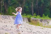 foto of little young child children girl toddler  - Adorable child little curly toddler girl in a blue summer dress running and playing on sand dunes in a beautiful pine wood forest enjoying hiking on a warm sunny day - JPG