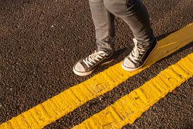 foto of street-walker  - walking on no parking yellow street lines - JPG