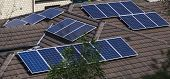 stock photo of roof tile  - Solar photovoltaic panels installed on tiled roof - JPG