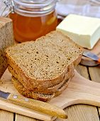 Rye homemade bread with honey and butter on board