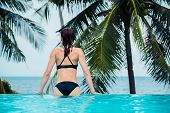 foto of infinity pool  - A young woman is sitting by the edge of an infinity pool by the ocean - JPG