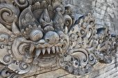 Balinese temple wall with traditional guard demon head