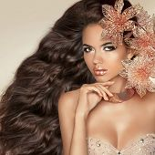 Long Wavy Hair. Beautiful Attractive Brunette Girl With Flowers. Healthy Hairstyle. Beauty Model Wom