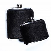 Metal flasks for alcoholic beverages on white.