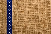 Dotted Ribbon On Burlap Cloth Background