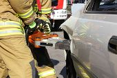 stock photo of spreader  - Firefighters open with a hydraulic rescue equipment the door of a car - JPG