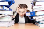 picture of boredom  - Frustrated businesswoman with stack of folders at office