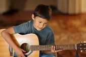 Young Boy Playing A Guitar