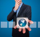 Earth in front of businessman. Touch screen consept - Stock Image