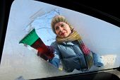 pic of scrape  - Winter scene adult woman scraping ice from windshield of car - JPG