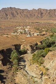 stock photo of hamlet  - Wadi Madbah with its traditional irrigation canal  - JPG