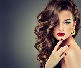 stock photo of lipstick  - Beautiful model brunette with long curled hair and fashion makeup - JPG