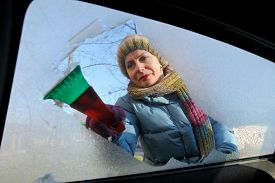 stock photo of scrape  - Winter scene adult woman scraping ice from windshield of car - JPG