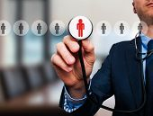 foto of recruiting  - Businessman hand with stethoscope - JPG