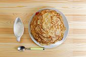 pic of frizzle  - Frying homemade pancakes with sour cream on wooden table - JPG