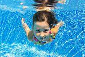 foto of swimming  - Child swims in swimming pool - JPG