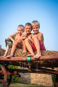 picture of hay bale  - boys sitting on a hay bale on sky background - JPG