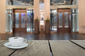 pic of elevator  - Defocus with terrace wood and cappuccino coffee with elevators in shopping mall for background usage - JPG