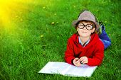 picture of 7-year-old  - Cute 7 years old boy lying on a grass and reading a book - JPG