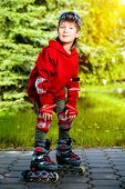 image of 7-year-old  - Cool 7 year old boy rollerblades on the street - JPG