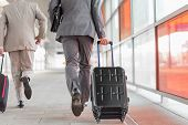 foto of carry-on luggage  - Rear view of businessmen with luggage running on railroad platform - JPG