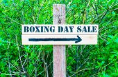 stock photo of boxing day  - BOXING DAY SALE written on Directional wooden sign with arrow pointing to the right against green leaves background - JPG